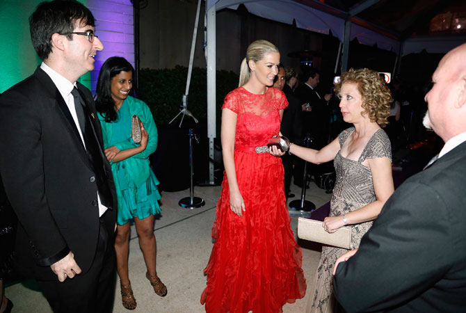 US Representative Debbie Wasserman Schultz (D-FL) (R), chair of the Democratic National Committee, greets comedian John Oliver (L) and his wife Kate Norley (2nd R) at the MSNBC after-party at the Italian Embassy, following the annual White House Correspondents' Association dinner in Washington.