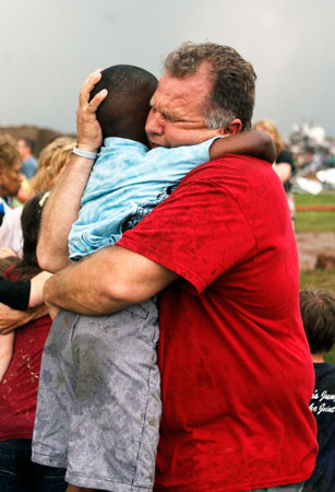 A teacher hugs a child at Briarwood Elementary school after a tornado destroyed the area. —AP Photo