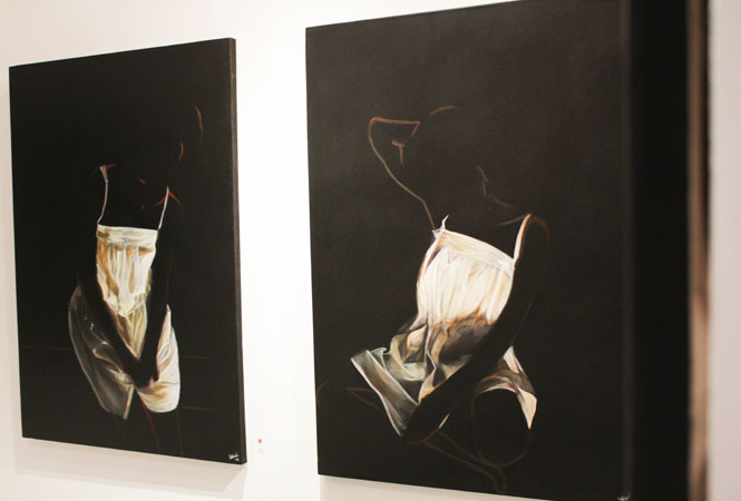 """Not again"" (right) and ""Matter of Indifference"" by artist Annem Zaidi. Using minimalism effectively, she casts into shadow the figure, and uses light to draw out the importance of the garment."