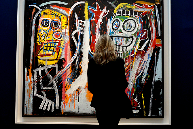 "This photo taken on May 3, 2013, in New York City, shows the painting ""Dustheads"" by Jean-Michel Basquiat on display during a preview of Christie's Impressionist and Modern Art sales. A blockbuster auction of Contemporary art in New York, including a record $58.4 million for a Jackson Pollock drip painting, fetched nearly half a billion dollars on Wednesday - the biggest haul ever at an art auction. Leading the frenzied charge were the Pollock and a work by one-time graffiti artist Jean-Michel Basquiat, which set a"