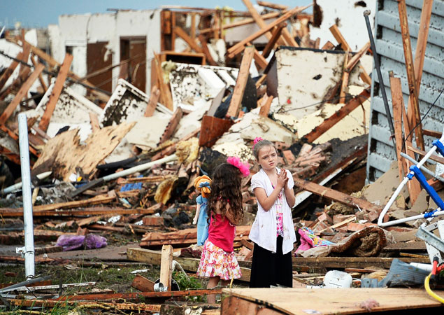Two girls stand in the rubble. —Reuters Photo
