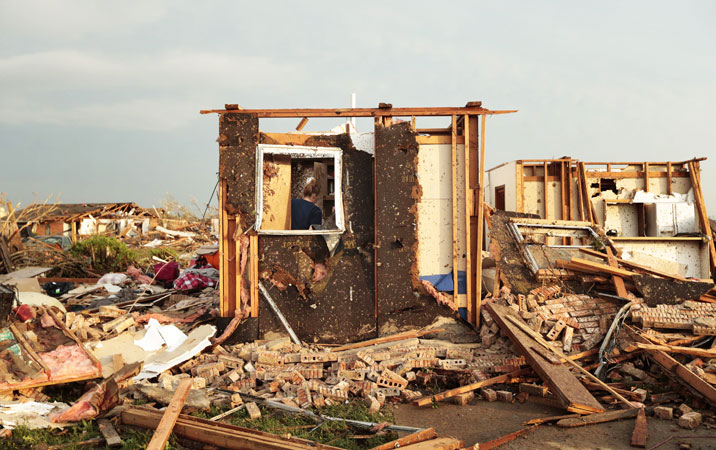 A woman searches inside a room left standing at the back of her house destroyed after a powerful tornado ripped through the area. —AFP Photo