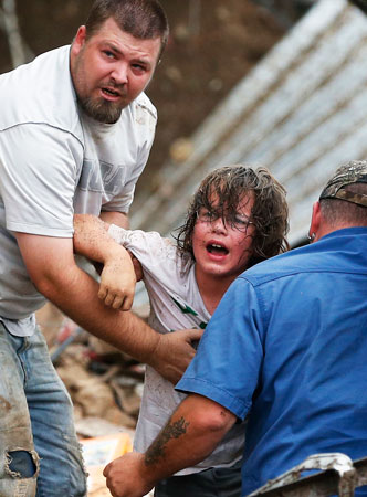 A child calls to his father after being pulled from the rubble of the Plaza Towers Elementary School. —AP Photo
