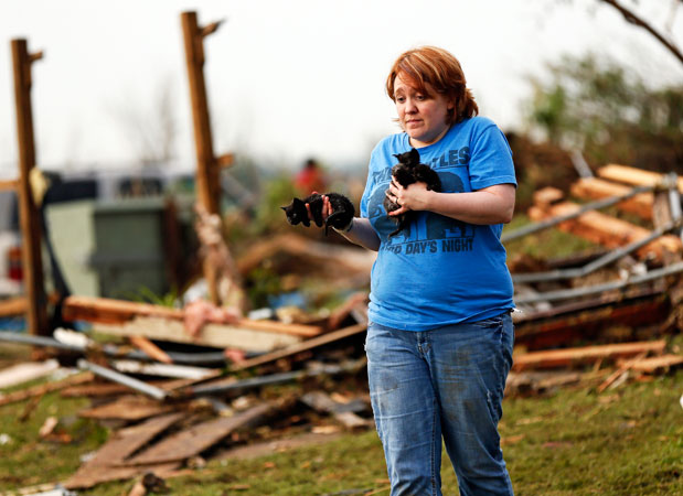 A woman holds stray kittens she found in the debris of her parents' home. —AP Photo