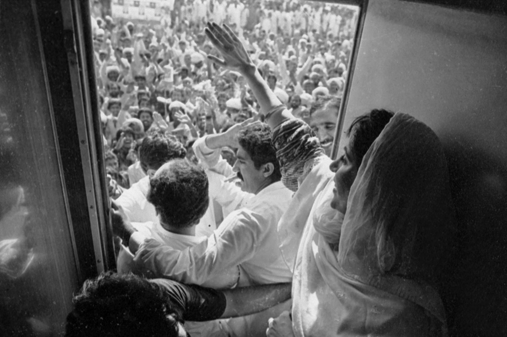 Benazir waves to the crowd from a bogie of a train during her 1988 election campaign.