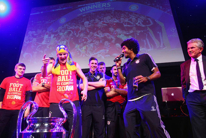 Bayern Munich's Toni Kroos (L), Bastian Schweinsteiger (centre L), Dante (centre R) and coach Jupp Heynckes (R) celebrate on stage at the team's banquet at Grosvenor House in London May 26, 2013, following their Champions League victory against Borussia Dortmund at Wembley stadium.