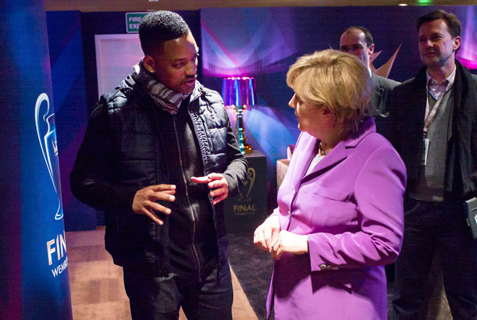 German Chancellor Angela Merkel talks with US actor Will Smith during half-time at the all-German Champions League final between Bayern Munich and Borussia Dortmund at London's Wembley stadium May 25, 2013, in this picture provided by BPA.