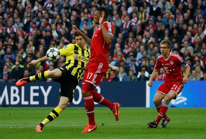 Borussia Dortmund's Robert Lewandowski (L) challenges Bayern Munich's Jerome Boateng.