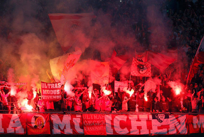 Bayern Munich fans light flares.