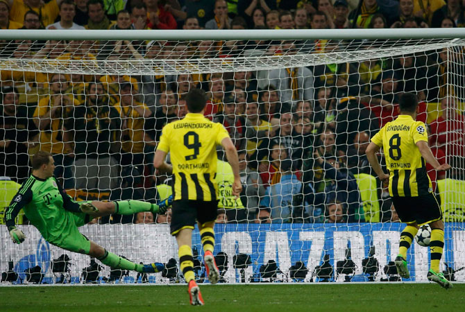 Borussia Dortmund's Ilkay Guendogan (R) scores a penalty past Bayern Munich's goalkeeper Manuel Neuer (L).