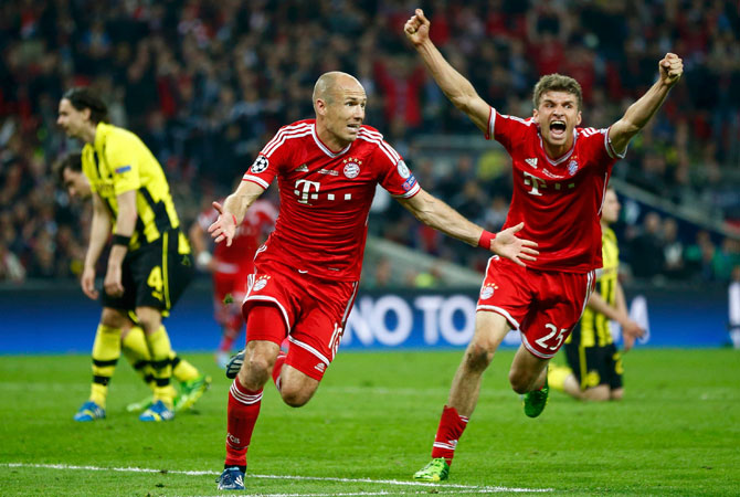 Bayern Munich's Arjen Robben (C), flanked by team mate Thomas Mueller (R), celebrates after scoring the winning goal against Borussia Dortmund.