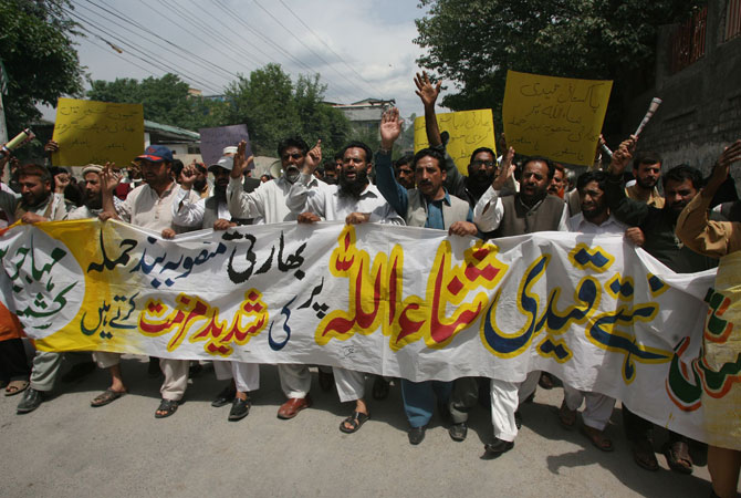 Kashmiri's shout slogans and wave placards as they march against the attack on Sanaullah Haq.