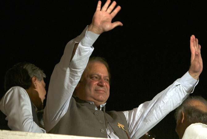 Former prime minister and PML-N leader Nawaz Sharif waves to his supporters at a party office in Lahore, May 11, 2013. Sharif declared victory following a historic election marred by violence Saturday, as unofficial, partial vote counts showed his party with an overwhelming lead. — Photo by AP