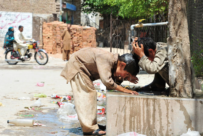 Boys cool themselves off in the burgeoning summer sun. The sight of disabled and disadvantaged children out on the streets is a constant reminder of the poverty prevalent in Pakistan's poor economic reality.