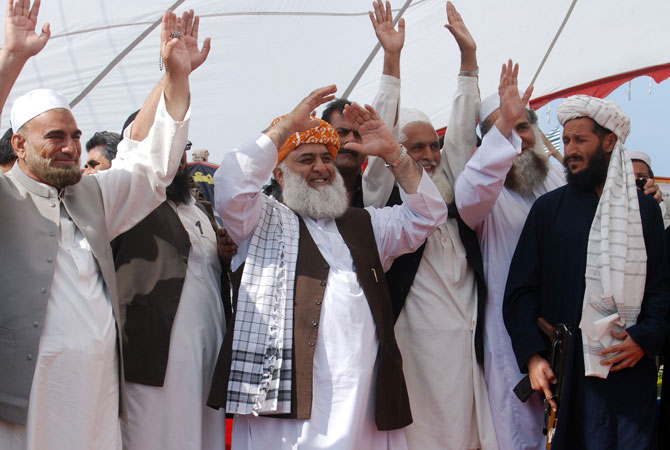 Maulana Fazalur Rehman (C, in brown vest), chief of the Islamic party Jamiat-e- Ulema Islam (JUI), waves to supporters during a parliamentary election campaign rally in the northwestern town of Mansehra on May 6, 2013.