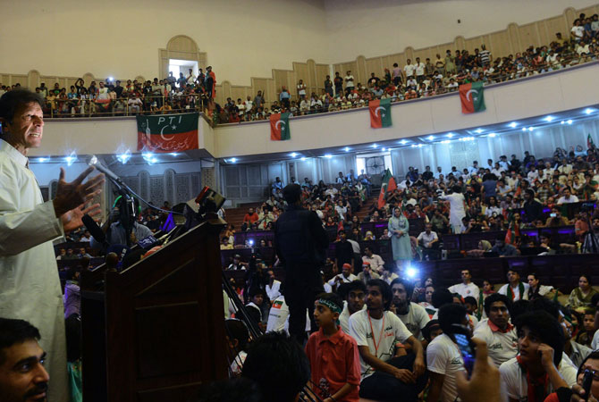 Pakistani cricket legend and chairman of Pakistan Tehreek-e-Insaaf (PTI) or Movement for Justice party, Imran Khan (L) addresses party workers and supporters at a ceremony in Lahore on May 5, 2013.