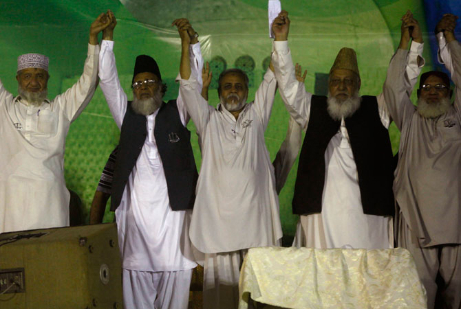 Syed Munawar Hassan (2nd L), leader of political and religious party Jamaat-e-Islami, joins hands with the party's local leaders during an election campaign rally in Karachi, May 5, 2013.
