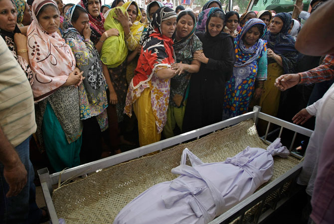 Pakistani women mourn next to the body of a child, who killed in the Saturday's bombing, during a funeral in Karachi, Sunday, May 5, 2013.