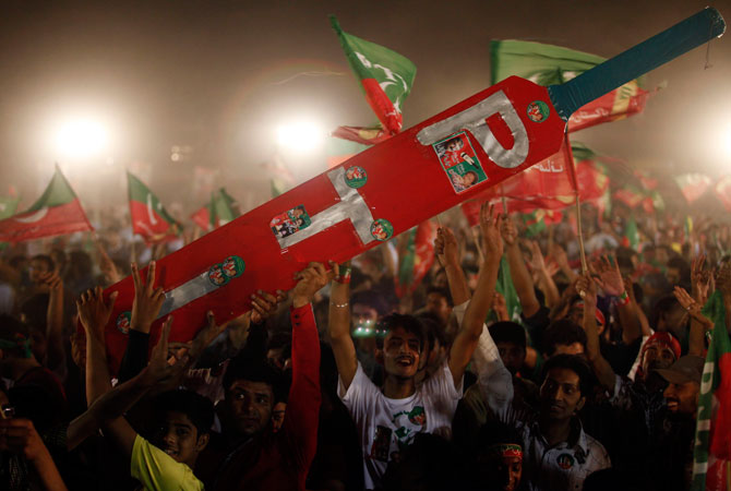 Supporters of Imran Khan, Pakistani cricketer-turned-politician and chairman of political party Pakistan Tehreek-e-Insaf (PTI) hold a large scale model of a cricket bat during an election campaign rally in Lahore, May 5, 2013.