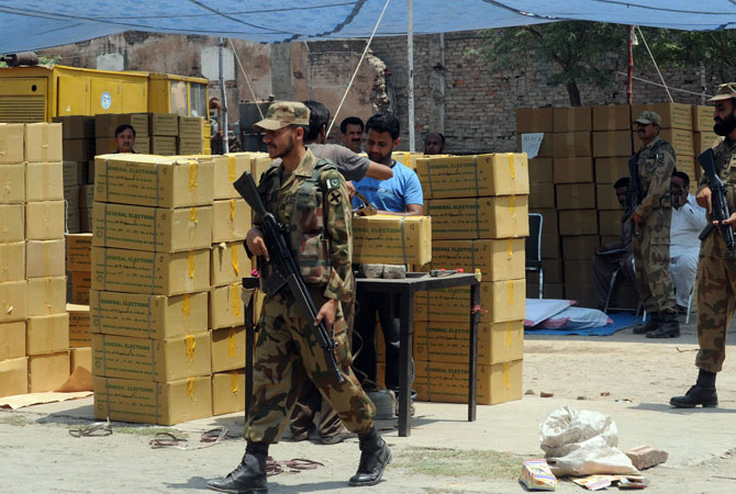Pakistani army soldiers stand guard beside boxes of electoral materials at the state-run Printing Corporation of Pakistan, before being transported to polling stations for the forthcoming parliamentary elections, in Lahore on May 6, 2013.