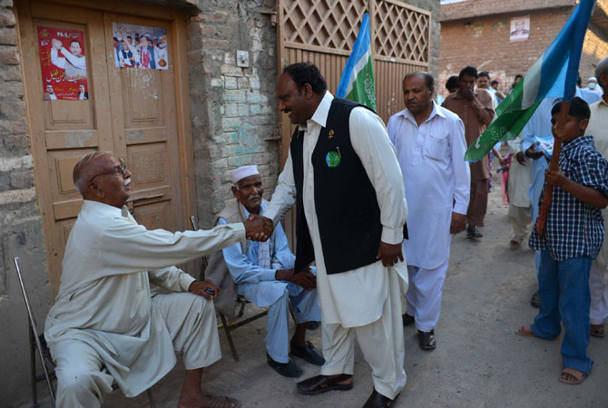 Pervaiz Masih (C), a Christian candidate of the Jamaat-e-Islami party for general election, meets with people at his election area in Peshawar.