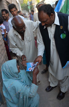 Pervaiz Masih (R) gives an election pamphlet to a Christian woman during his election campaign.