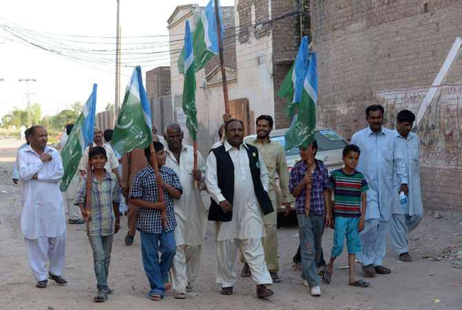 Pervaiz Masih (C) walks with supporters.
