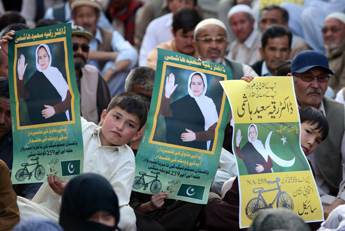 Hazara Shia community members and supporters of Ruquiya Hashmi, carrying electoral posters as they take part in an election campaign meeting.