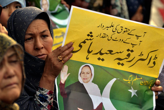 A woman holds a poster of Ruquiya Hashimi during her election campaign rally.