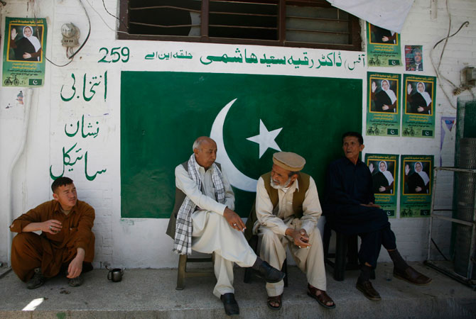 People lean against a wall with posters of Ruquiya Hashimi and a painting of Pakistan's national flag outside her election campaign office.