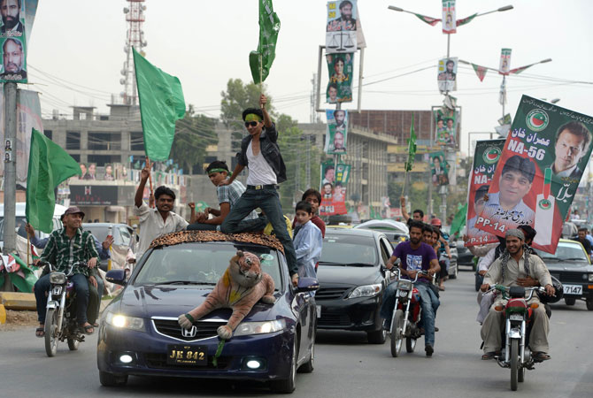 Activists of Pakistan Tehreek-e-Insaf (PTI) and Pakistan Muslim League Nawaz (PML-N) parties carry posters and flags as they drive during the general election in Rawalpindi.