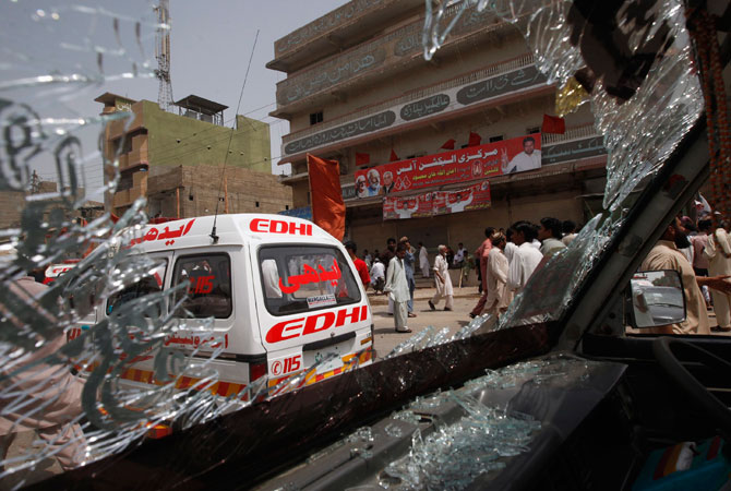 Security officials and residents are seen through the shattered windscreen of a damaged vehicle at the site of a bomb attack in Karachi.
