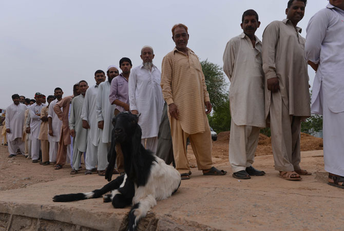 Pakistani voters stand in a queue waiting for their turn outside a polling station in Islamabad.