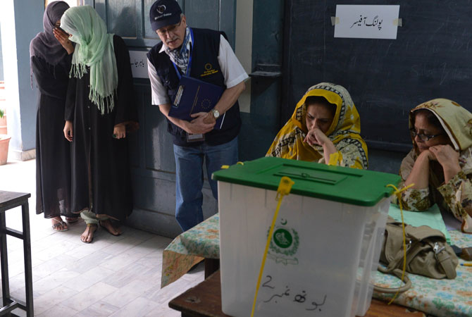 A European Election Observation Mission official (C) monitors polling as female voters (L) wait for their turn to cast their vote at a polling station in Islamabad.