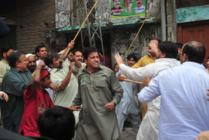 Pakistani political party activists clash near a womens polling station after an incident during voting for the general election in Rawalpindi.