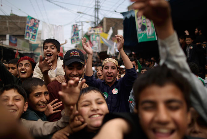 Pakistani youth supporters of former cricket star-turned-politician, and leader of Pakistan Tehreek-e-Insaf party, Imran Khan, chant slogans in Khan's support near a polling station in Rawalpindi.
