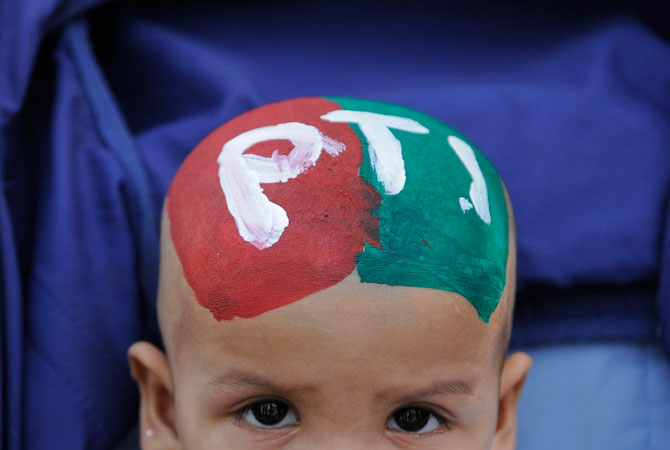 Mohammad Ahmed, 1, with his head painted with the flag and name of Pakistan's Tehrik-i-Insaf party (PTI) waits in his stroller as his mother (not pictured) waits for her turn to cast her vote at a polling station in Karachi.