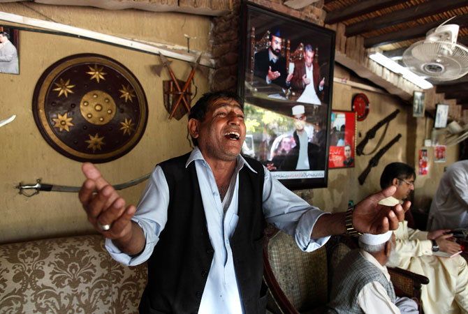 A man sings to entertain visitors who have come to seek help at the house of Haroon Bilour.