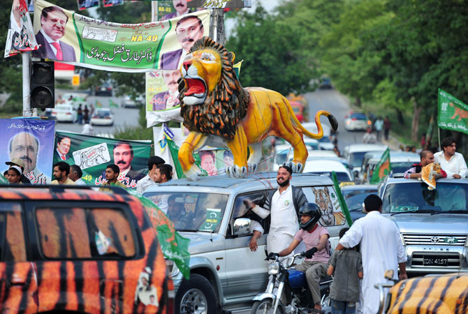 Supporters of Pakistan Muslim League Nawaz (PML-N) march in a rally along with a statue of a lion, the party election symbol for the upcoming general election in Islamabad.