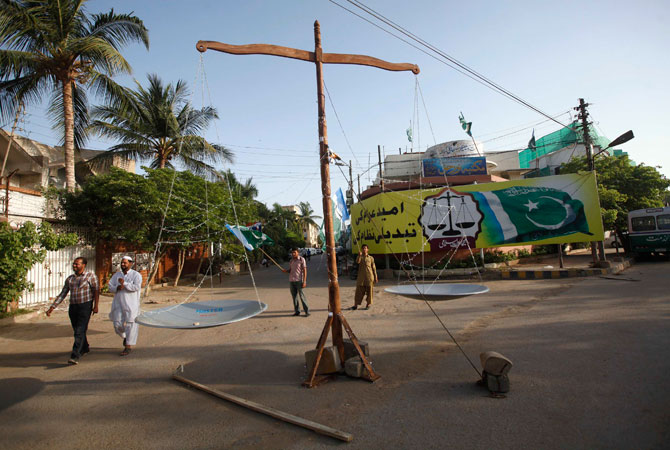 Supporters of the political and religious party Jamat-e-Islami wave a flag next to a giant party symbol of a scale along a roadside in Karachi.