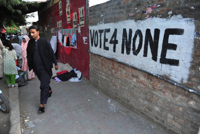 Pakistani youth walk past a wall with graffiti of populist cleric Tahir-ul-Qadri party in Islamabad after his party boycotted the general election. Qadri announced that his party will boycott the upcoming parliamentary elections as old faces will return to the parliament and there will be no positive change.