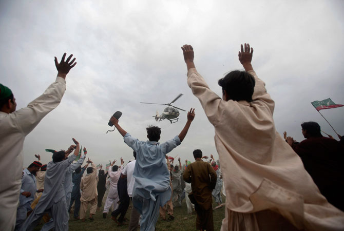 Supporters wave towards a helicopter transporting Pakistan Tehreek-e-Insaf's (PTI) Chief Imran Khan as he leaves after his election campaign rally in Nowshera, Khyber Pakhtunkhwa province.