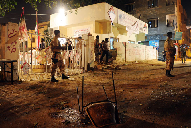 Pakistani security officials cordon off the site of twin bomb blasts near the secular Muttahida Qaumi Movement (MQM) party office in Karachi on May 4, 2013. Three people were killed and more than 20 others wounded in the blasts near the local party office, police said, ahead of next week's historic elections.