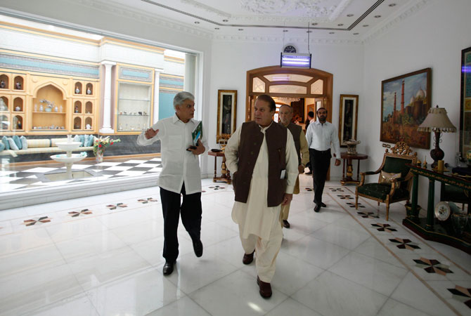 Nawaz Sharif (R) leader of political party Pakistan Muslim League - Nawaz (PML-N) walks with his personal secretary Asif Kirmani at his house in Lahore. Sharif, seen as the front-runner in Pakistan's election race, said the country should reconsider its support for the US war on Islamist militancy and suggested that he was in favour of negotiations with the Taliban.