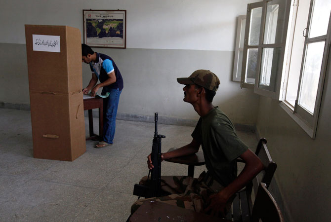 An army soldier (R) sits on a chair while a voter stamps his ballot papers inside a booth at a polling station during re-polling for the general elections in Karachi, May 19, 2013. Sunday's voting took place at 43 polling stations across the constituency and, for the first time, each ballot box was guarded by a ranger and a soldier inside the booth instead of outside.