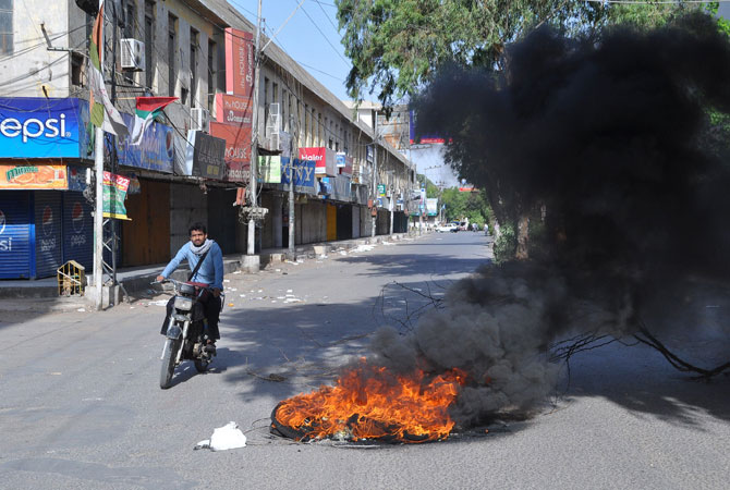 A Pakistani man rides past burning tyres set on fire by protesters demonstrating against Imran Khan in Hyderabad on May 19, 2013.
