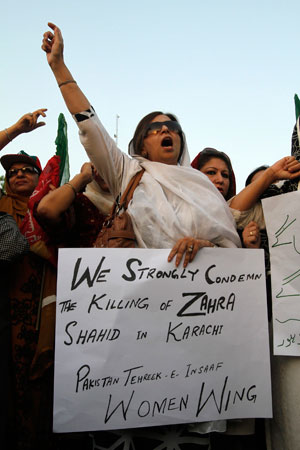 A supporter of the Pakistan Tehreek-e-Insaf (PTI) political party of cricketer-turned-politician Imran Khan holds a placard as she shouts slogans with others during a protest against the killing of Zahra Shahid Hussain, a leading member of the PTI, in Lahore on May 19, 2013.
