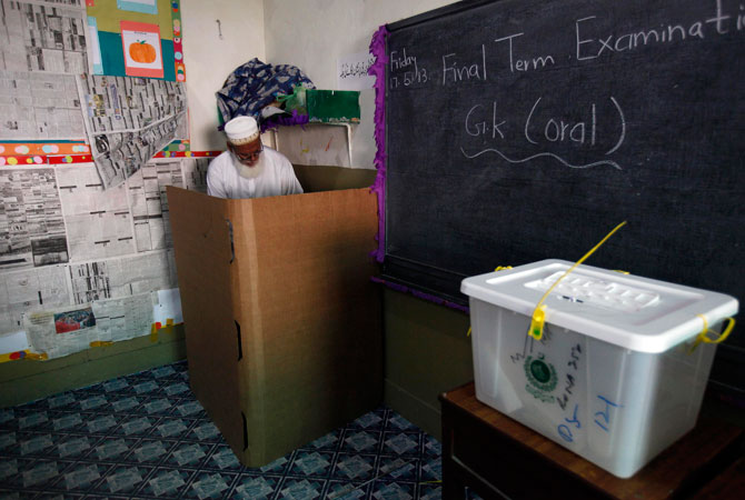 A voter stamps his ballot papers inside a booth at a polling station during re-polling.