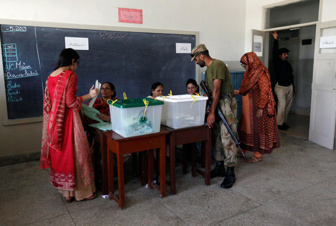 An army soldier talks to election officials whom female voters go to for their ballot papers, inside a booth at a polling station during re-polling.
