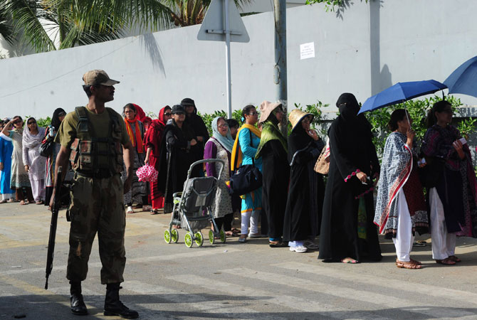 Pakistani army soldiers stand guard at a polling station as women queue to cast their ballots during the re-poll of voters in the constituency known as NA-250 in Karachi on May 19, 2013.  Hundreds of people queued up at 43 polling stations in a constituency of Pakistan's port city of Karachi on Sunday where a re-vote had been ordered over allegations of ballot stuffing.